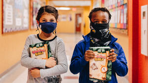 First graders in masks with bibles