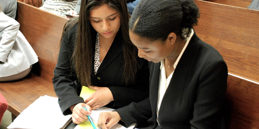narrow two students conferring over notes mock trial